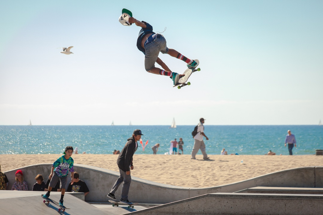 ninos y adolescentes patinando en la playa