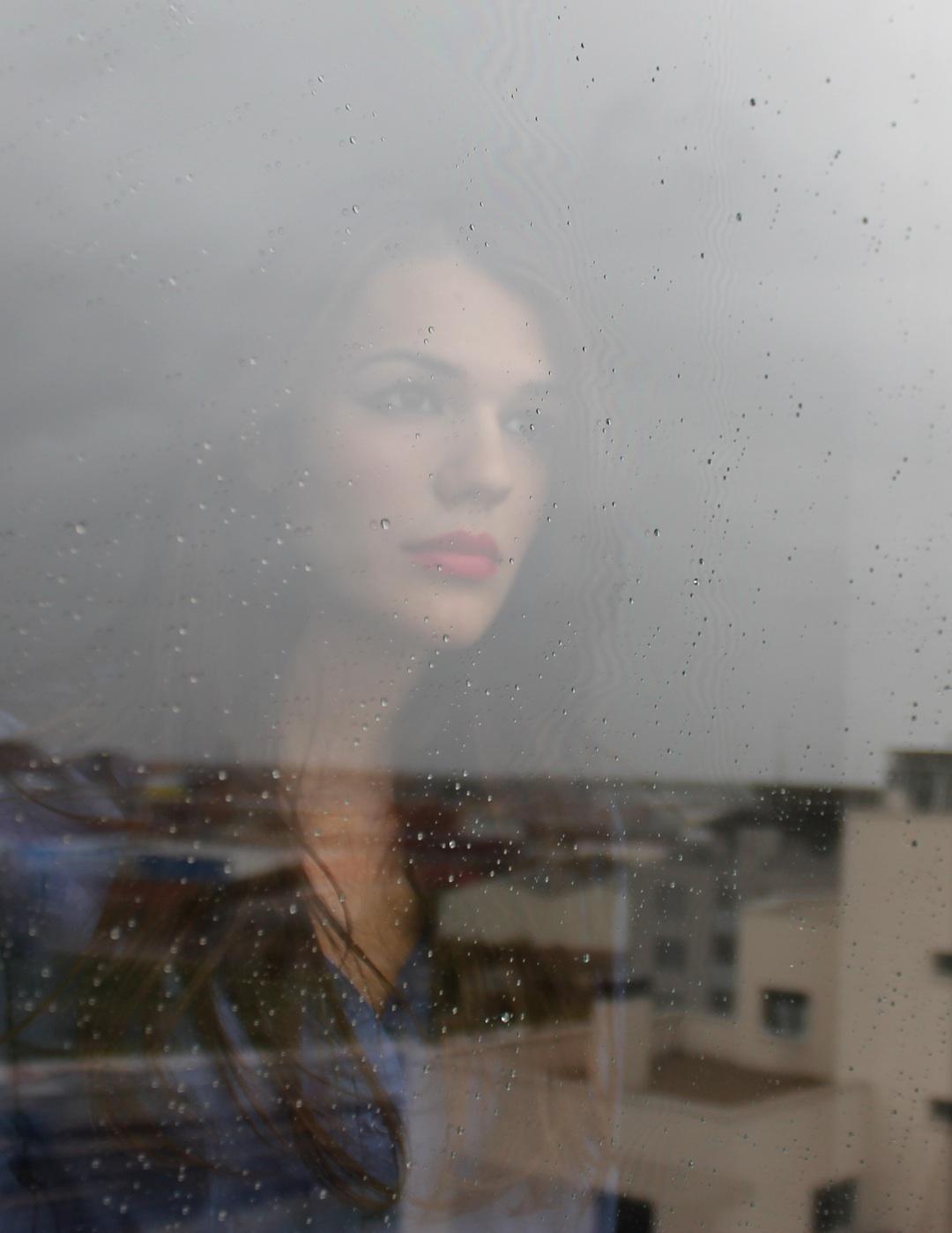 chica triste tras cristal con lluvia