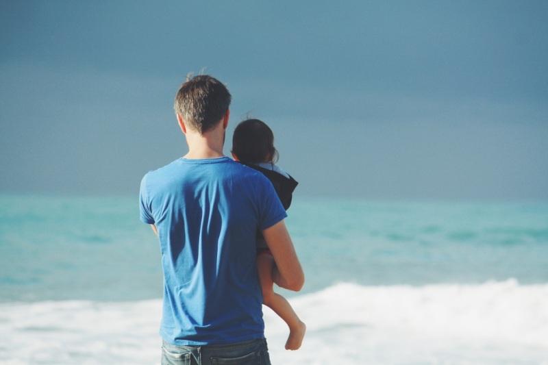 padre con nino en brazos mirando al mar