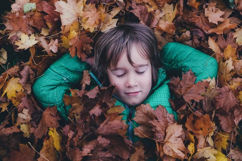 nino tumbado en las hojas de otono