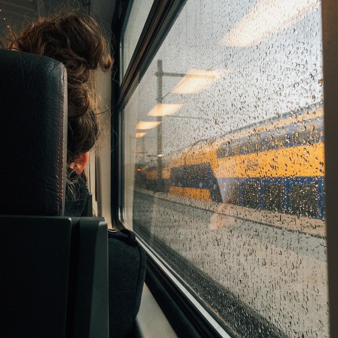 chica en tren lloviendo