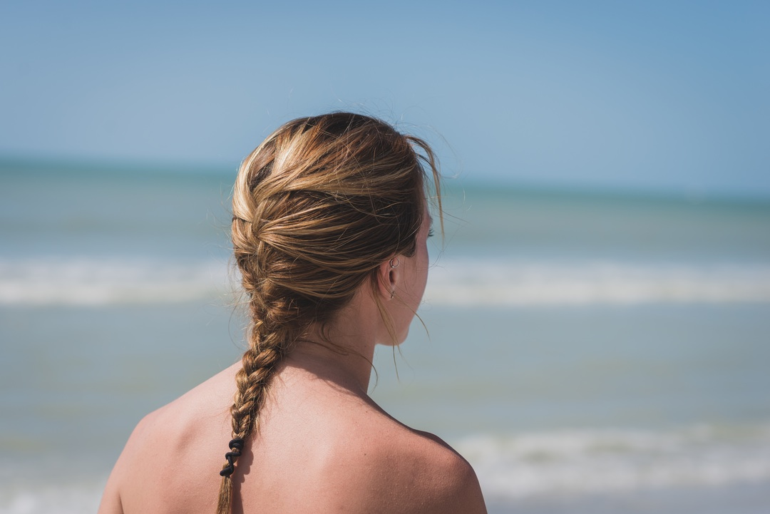 mujer con trenza mirando al mar